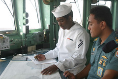 SURABAYA, Indonesia (May 9, 2011) Quartermaster Seaman Clay Saa makes plot markings on a chart on board USS Guardian (MCM 5) with Lt.j.g. Tato Taufiq of the Indonesian navy. Taufiq was one of two Indonesian ship riders who transited with Guardian from Bali to Surabaya. (U.S. Navy photo)