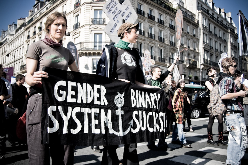 "a protest where two people are holding a sign saying ""gender binary sucks"""
