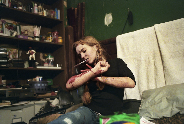 The Ninth Floor, Natasha, who slept in the secret space behind a movable bookcase, bloodies her arms as she struggles for 45 minutes to find a vein in New York, 2005, by Jessica Dimmock