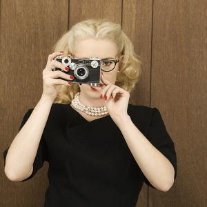 woman holding a vintage camera up to her face