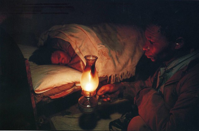 South African farm worker brings a lamp to his wife's bed at 6 am to wake her for her job, just before he leaves home for the fields. She works as a domestic servant for the same white farmer, by David Turnley 1990
