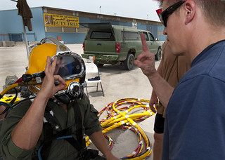 Navy diver gives an okay to another diver after completing a pre-dive inspection