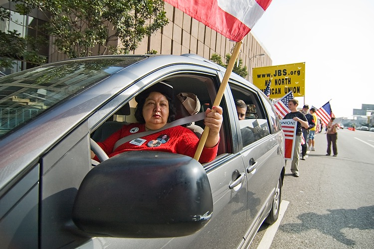 A driving marcher holds an American flag out of her window to protest a North American Union on November 17, 2007 in West Los Angeles.