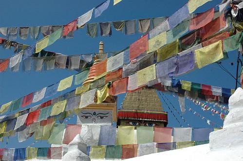 Boudha Wishfulfilling Stupa looking over colorful rows of Tibetan Prayer Flags in the east, Kathmandu, Nepal by Wonderlane