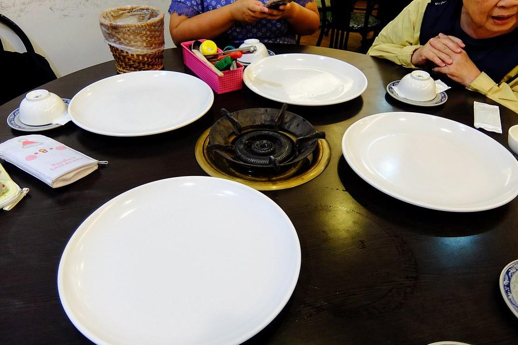 桌子,中間有一鍋爐,旁邊有四個盤子待會要來裝蒸籠