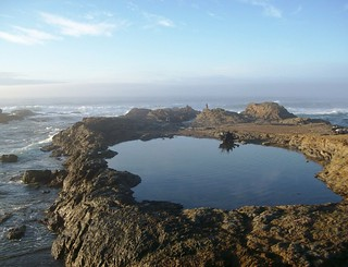 Isolated tidal pool, with the raging waves of the Pacific Ocean in the background, at Glass Beach, CA (glassbeach06xy)
