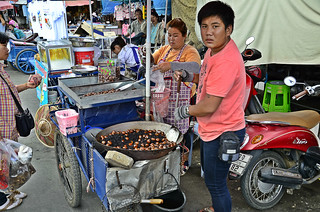 A boy and his mother selling chestnut along the street .