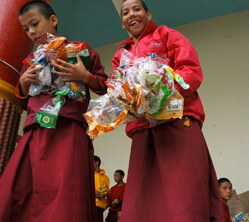 All eagerness - Packing up the offerings of candy and fruit, young monks, Tharlam Monastery of Tibetan Buddhism, Boudha, Kathmandu, Nepal by Wonderlane