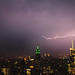 Lightning streaks toward the Empire State Building, as seen from Rockefeller Center