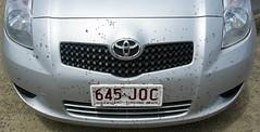wheel(0.0), rim(0.0), automobile(1.0), automotive exterior(1.0), toyota(1.0), vehicle(1.0), toyota vitz(1.0), bumper(1.0), land vehicle(1.0), vehicle registration plate(1.0),