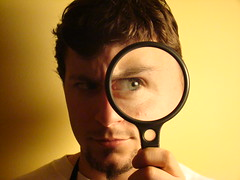 young man with short brown hair looking through a magnifying glass