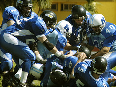 huddle(0.0), football(0.0), arena football(0.0), american football(1.0), football--equipment and supplies(1.0), sport venue(1.0), football helmet(1.0), sports(1.0), tackle(1.0), player(1.0), gridiron football(1.0), canadian football(1.0), athlete(1.0), team(1.0),