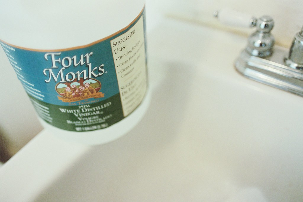 white distilled vinegar ready to create clean bathroom sink