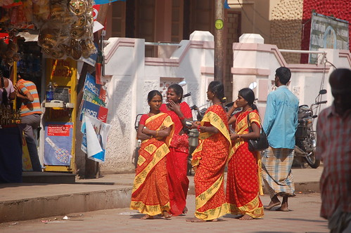 In der Fußgängerzone von Madurai spazieren vier Frauen mit roten Saris.