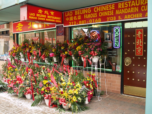 The front of Lao Beijing Chinese restaurant. Dozens of flower baskets cover the windows all the way to the large red and gold store front signs.