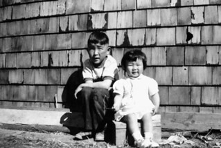 Eugene Hattori, first child of interned Japanese parents, and his sister Susan, Lethbridge, Alberta / Eugene Hattori, premier enfant né à Lethbridge, en Alberta, de parents japonais en camp d'internement. Il est photographié avec sa sœur Susan