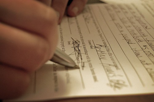 Photograph of a contract which has just been signed; a right hand holding a pen is poised above the paper.