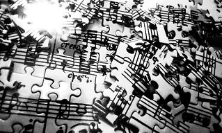 Strewn pieces of a jigsaw of a musical score