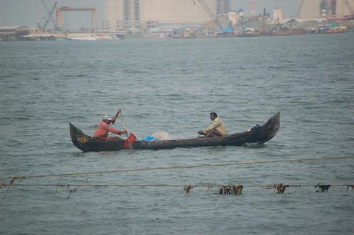 An der Einfahrt zum Hafen, der von später von den Engländern errichtet wurde, sind Fischer im Einbaum unterwegs, deren Fang in Plastiksäcken verpackt. Im Hintergrund ein Containerhafen und ein Zementwerk