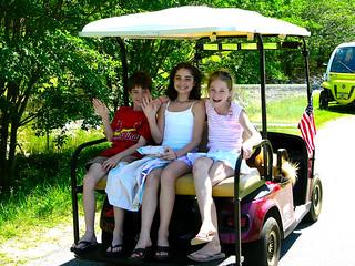 family on back of golf cart