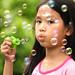 A little girl blowing soap bubbles in garden 1-1 by mmkamy17