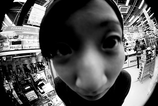 Black and white photo of a young adult looking into a security camera. The photo is distorted.