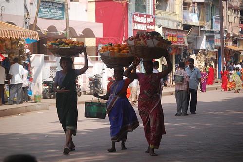 Durch die Fußgängerzionen gehen drei Frauen mit Obstschalen auf dem Kopf
