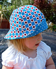 beanie(0.0), knit cap(0.0), child(1.0), pattern(1.0), clothing(1.0), sun hat(1.0), hat(1.0), cap(1.0), pink(1.0), toddler(1.0), headgear(1.0),