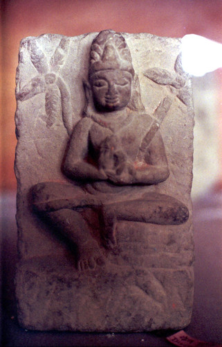 Stone statue of Lord Buddha as a meditator (wearing a mediation strap and a crown) seated with mudra, Kusinara, India by Wonderlane