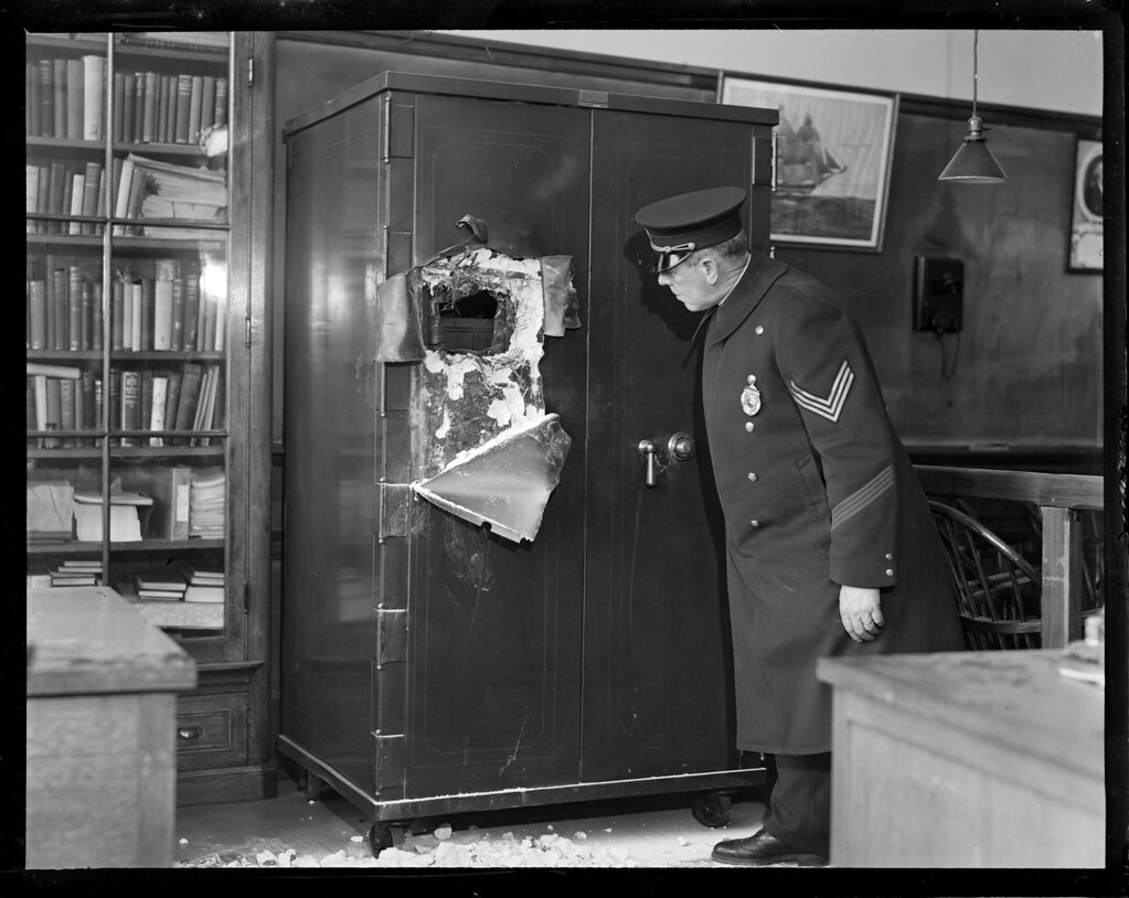 Sgt. F.V. Sullivan examining safe that youths, Theodore McDonald, Albert Monichiello, and Henry J. Benda tried to crack.