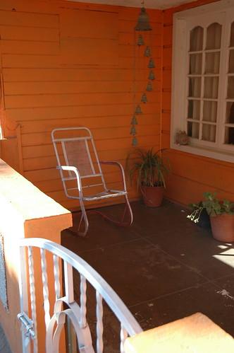 Orange walls, white rocker, rhythm of bells, white gate, white trimmed windows, patio, City of Wood, San Rosalia, Baja California Sur, Mexico by Wonderlane