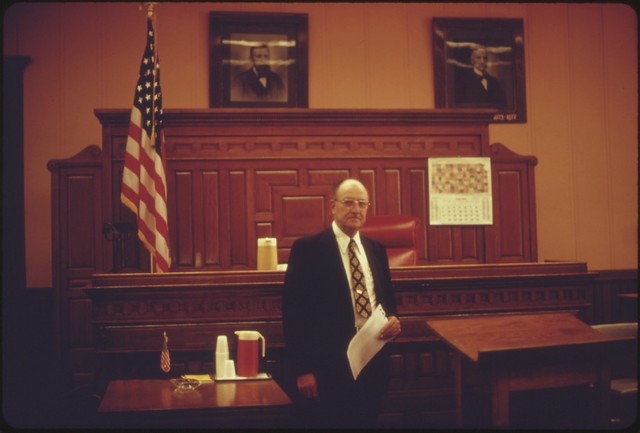 An Official in the Atchison County Courthouse in Atchison Kansas, Stands in the Building's Courtroom...06/1974