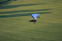 parachute(0.0), adventure(1.0), aviation(1.0), field(1.0), grass(1.0), wing(1.0), vehicle(1.0), air sports(1.0), sports(1.0), recreation(1.0), plain(1.0), glider(1.0), outdoor recreation(1.0), windsports(1.0), hang gliding(1.0), gliding(1.0), green(1.0), aerial photography(1.0), grassland(1.0), flight(1.0),