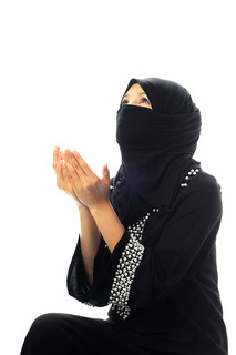 A muslim women pray looking up from side