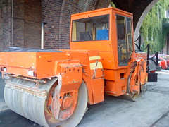 light commercial vehicle(0.0), bulldozer(0.0), tractor(0.0), asphalt(1.0), vehicle(1.0), transport(1.0), road roller(1.0), compactor(1.0), construction equipment(1.0), land vehicle(1.0),