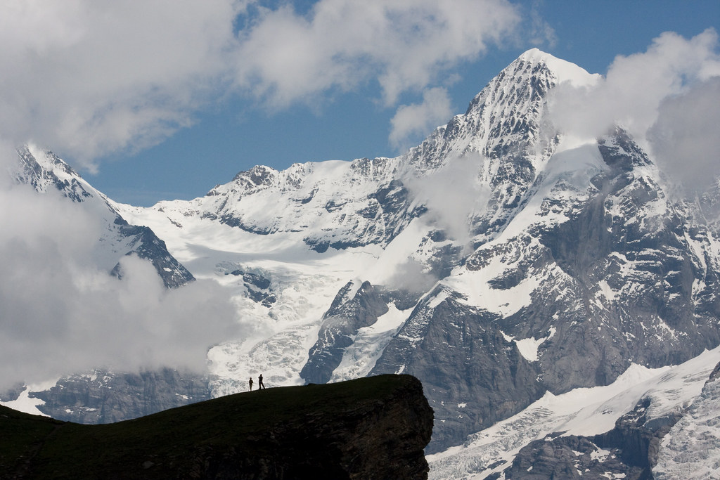 Two climbers in the Bernese Alps of Switzerland stand on a precipice across from a large mountain peak shrouded in clouds called the Mönch.