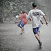 Teenagers playing soccer in the rain