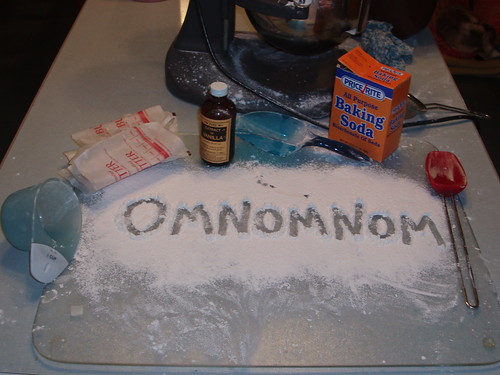 the word omnomnom written in flour on a countertop, with various cooking items around it