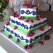 Three tier square wedding cake. Fondant covered with purple scrollwork and fresh purple orchids