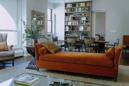 velvet daybed painted bookshelves in open plan living dining room