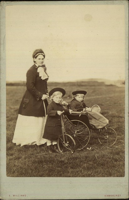 Outdoor portrait of a mother, or nurse, pushing a baby in a pram and with a young child with a bicycle by E Williams of Kent, 1890-1900.