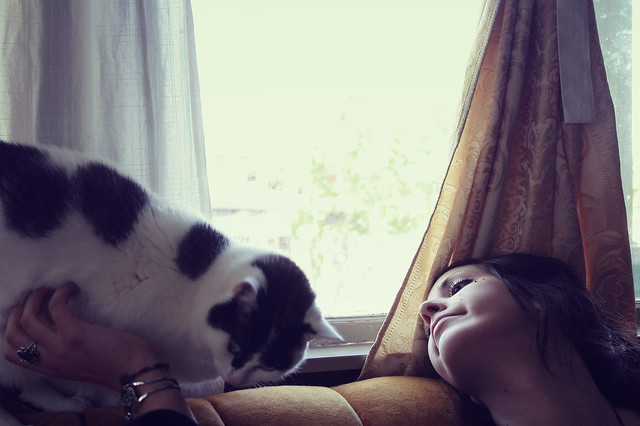 Woman with cat, daydreaming