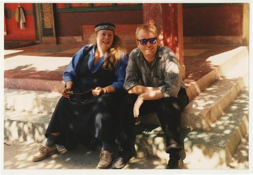 Buddies - Jean Freeman wearing a Tibetan chuba, holding a mala, and her friend Malcolm, Buddhist students, Tarig Monastery stairs, Sakya Lamdre, Boudha, Kathmandu, Nepal 1990 by Wonderlane