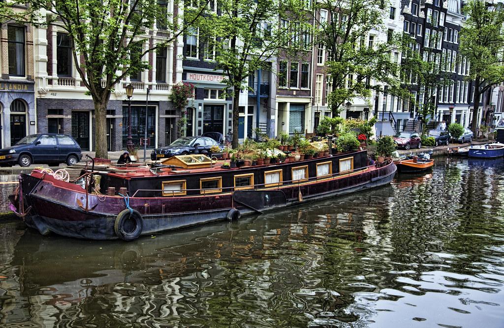 Photo typique d'Amsterdam avec sur fond de canal bordé de maisons étroites aux fenêtres omniprésentes mouille une mignonne péniche fleurie. Photo de vgm8383