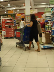 Woman Walking with Shopping Cart inside a Supermarket.