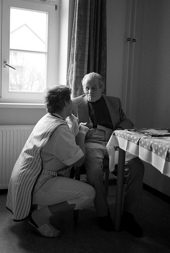 care giver and elderly man sit together