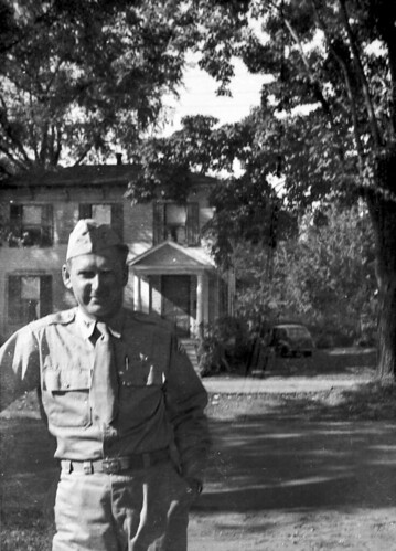 Man in uniform in front of house