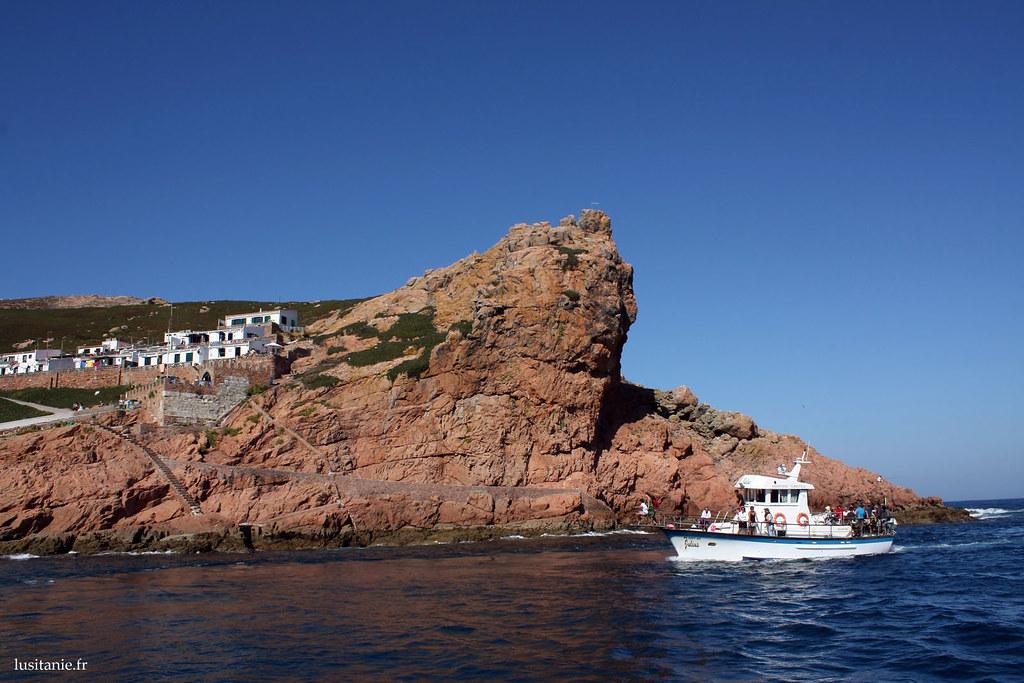 Le paysage de cette petite île de l'océan Atlantique est de toute beauté, comme peuvent le voir les gens du bateau qui passent devant ce gros rocher.
