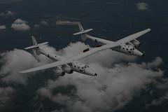 VMS Eve soars through the clouds above Oshkosh. Credit Mark Greenberg