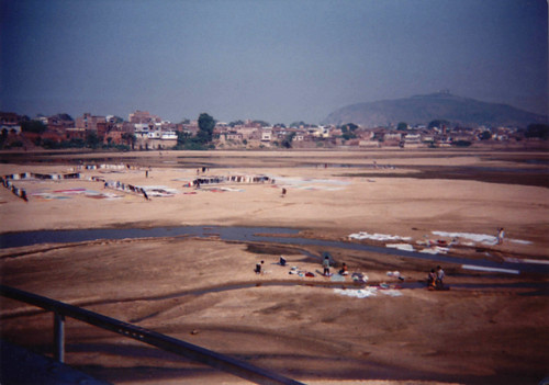 View of wallas washing clothes in a river and hanging them to dry, from a Buddhist pilgrimage tour bus, on a bridge, town, Northern India, 1993 by Wonderlane